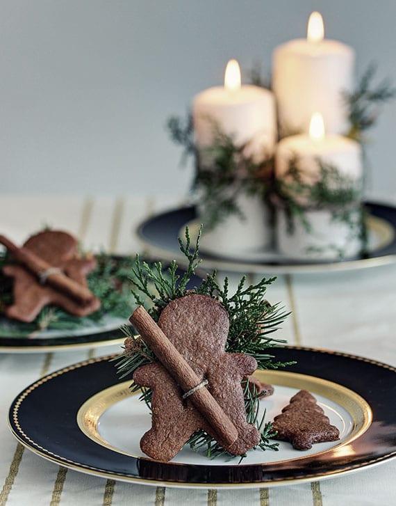 kreative platzteller deko zu weihnachten mit Lebkuchenmänner, Zimtstabgen und frischem Grün