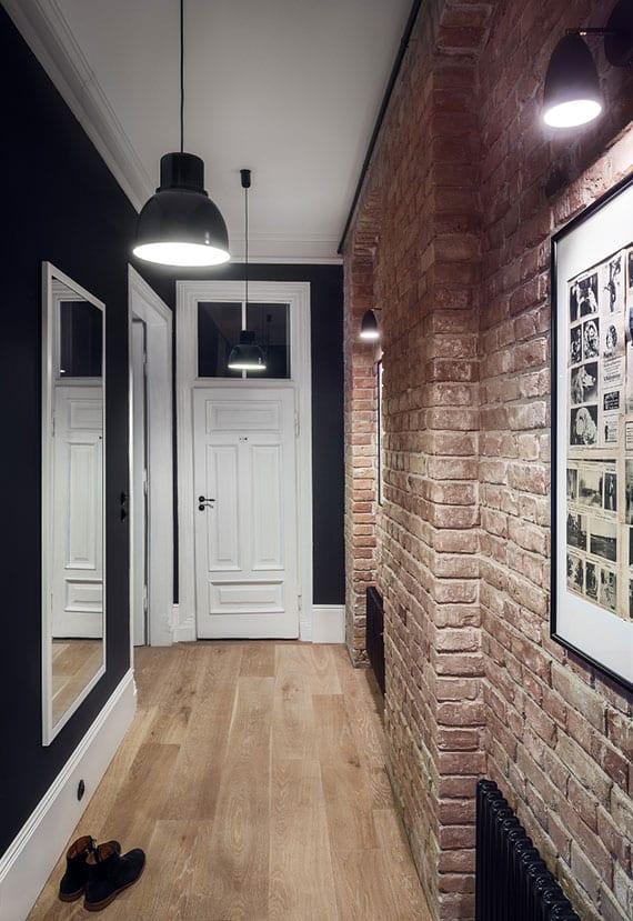 die schmale diele attraktiv gestalten mit parkettboden, ziegelwand, großem dielenspiegel, vintage-leuchten und wandfarbe schwarz