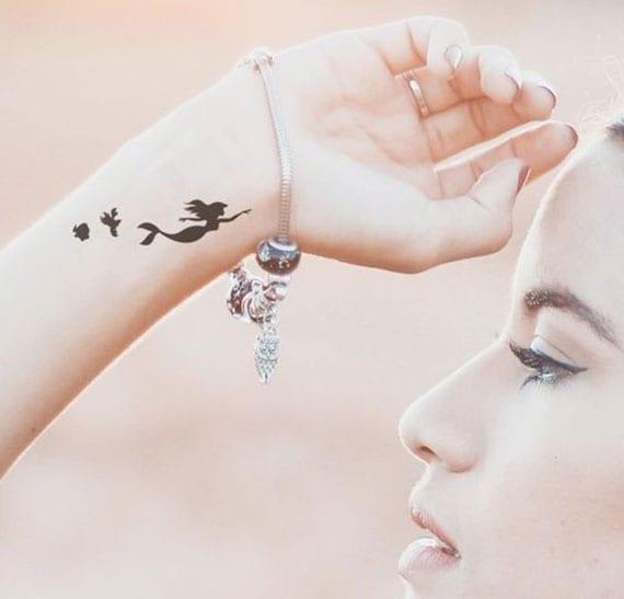 arielle als kleines solid black disney tattoo für frauen