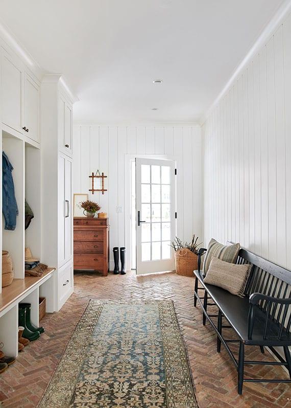 designideen für wandgestaltung im eingangsbereich mit weißen holzpaneelen und offener garderobe