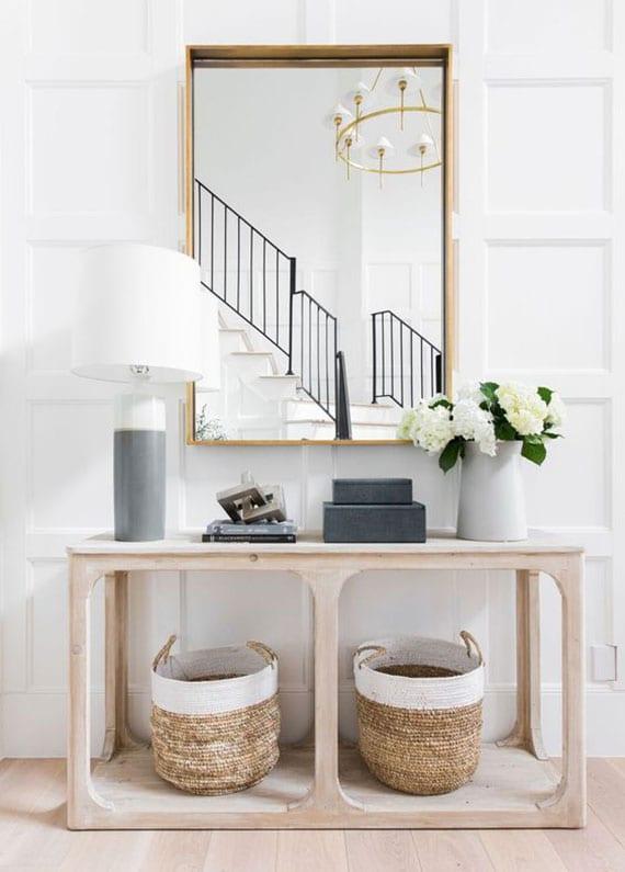 diele hell und einladend einrichten mit designer flurtisch aus holz, weidenkärben, flurspiegel in goldrahmen, tischlampe und blumenvase aus keramik