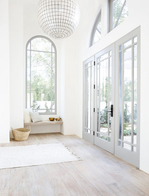rustikale hausdiele mit grauen sprossfenstern, weißen wänden, hellem holzbodenbelag und holzsitzbank in wandnische