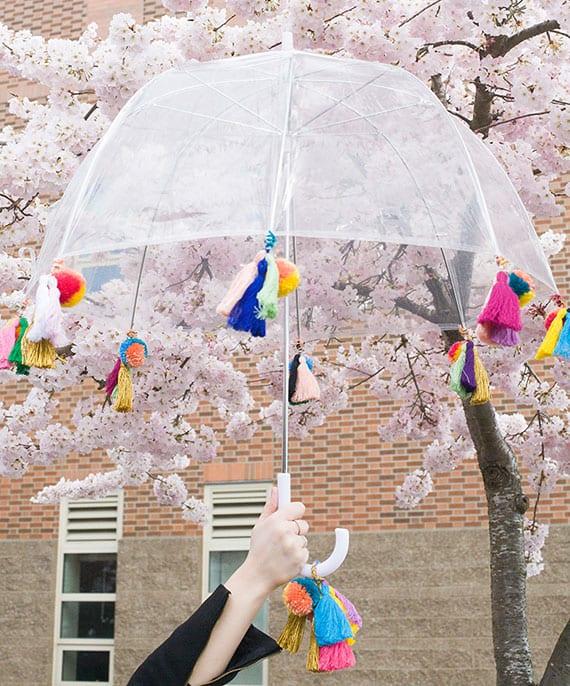 der regenschirm als geschenkidee und mode-accessoire im boho stil mit bunten quasten und pompoms