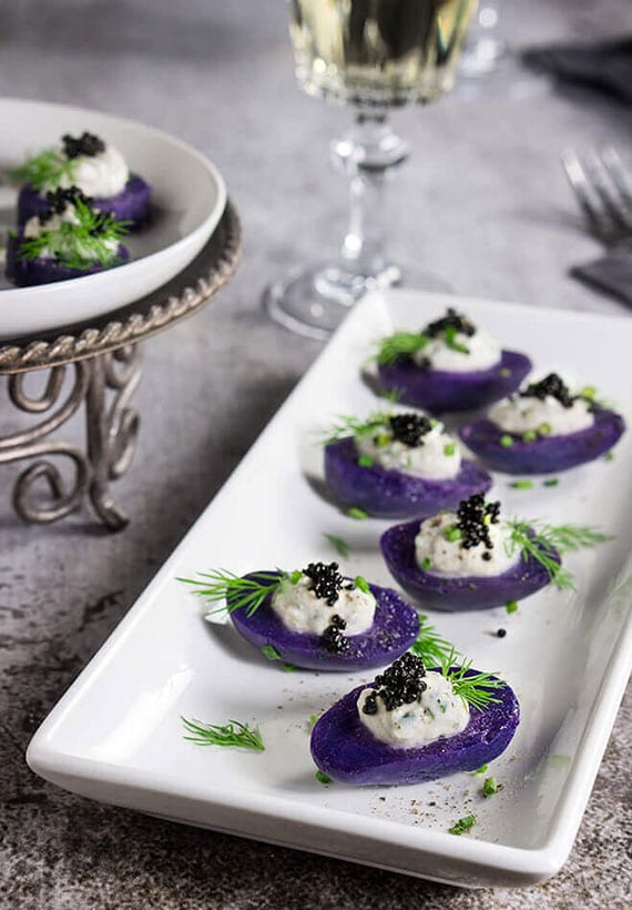 ausgezeichnete häppchen aus lilafarbigen kartoffeln mit Meerrettich-Frischrahm und Kaviar