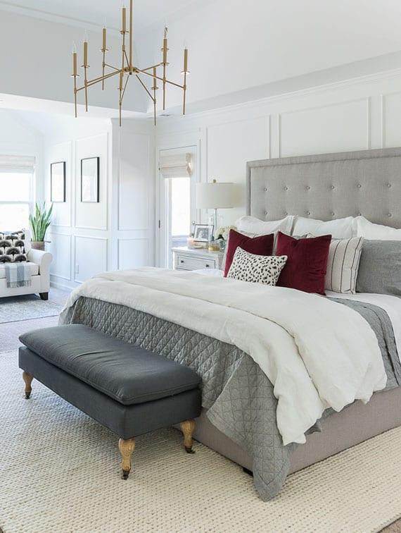 gemütliches schlafzimmer interieur in weiß mit polsterbank vor box-spring-bett mit gepolstertem kopfteil in grau und sitzecke mit zwei sesseln