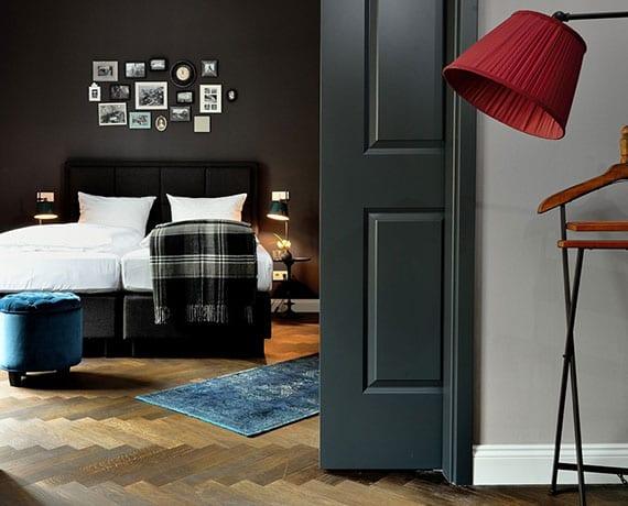 attraktive gestaltungsidee für schlafzimmer in schwarz mit parkettboden, box-spring-bett mit kopfteil in schwarz und farbakzente in blau