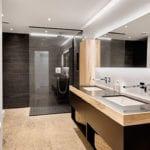 stilvolle badgestaltung mit akzenten in schwarz und holz, doppelwaschtisch mit unterschrank und wandverkleidung mit naturstein im duschbereich