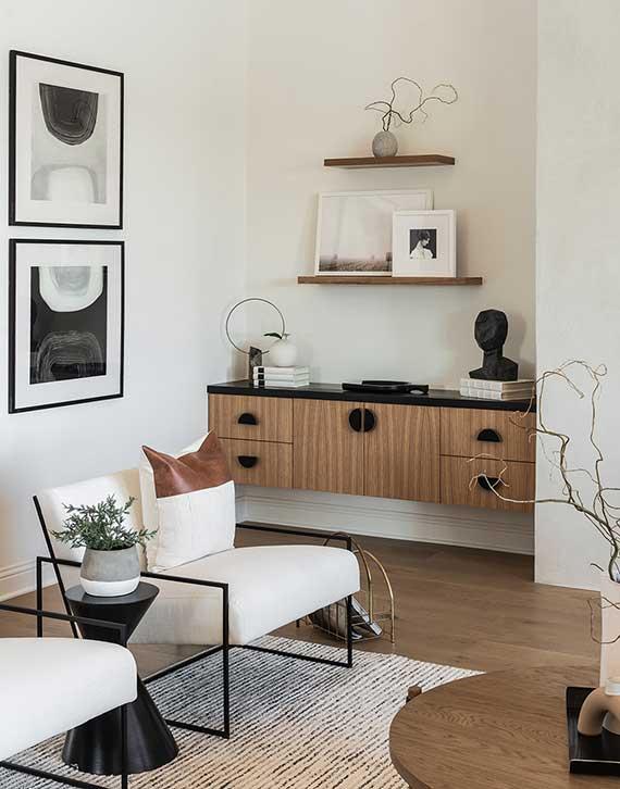 elegantes wohnzimmer interieur im klassischen stil mit akzenten in schwarz,holzhänheschrank und wandregale als stauraum in wandnische, wanddeko mit abstrakten bildern, sitzecke mit weißen polstersesseln und rundem holzcouchtisch