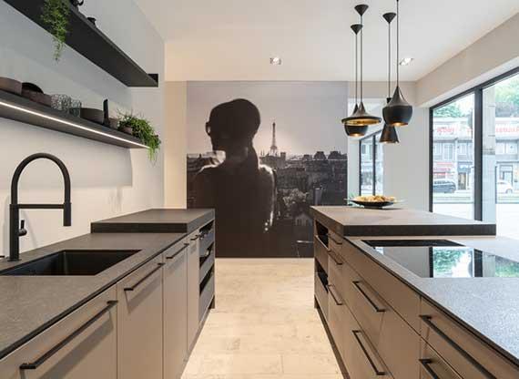 moderne küche in beige mit schwarzer küchenarbeitspaltte, kochinsel, wandregallen und attraktive wanddeko mit schwarzweißer Paris Fototapete