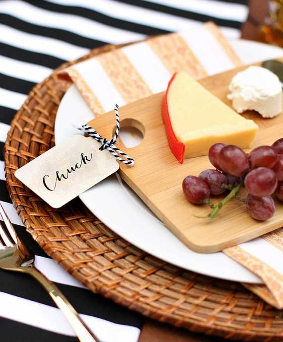 schänes tischgedeck mit tischset aus runden rattanplatten und Mini-Käsebrett als Tischkarte im Platzteller