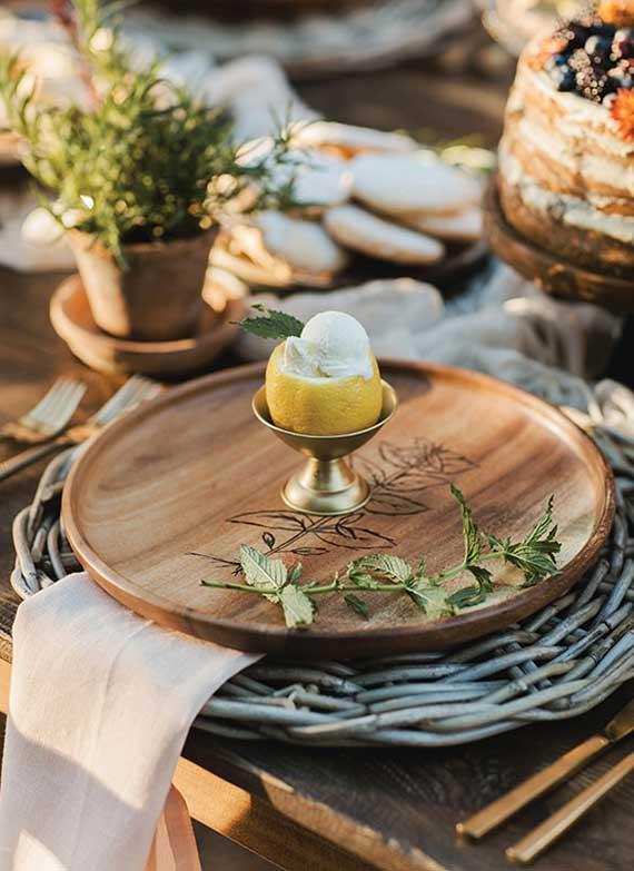 natürliche herbsliche tischdekoration mit tischset aus runden Rattanplatten und Holzplatztellern