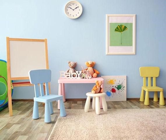 Innenraumgestaltung fürs kinderzimmer mit wandfarbe blau, mitwachsenden kindermöbel in pastellfarben und gemütlichen teppichboden