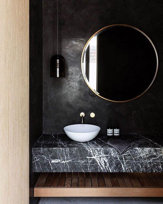 badmöbel trends 2021-attraktive badezimmer gestaltung in schwarz mit waschtisch naturstein, rundem badspiegel und hängelampe in kleiner wandnische