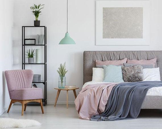 schlafzimmer farbgestaltung mit beruhigender Wirkung_textilien und möbelstücke in rosa und blau als schlichte farbliche akzente zu weißen wänden im schlafbereich