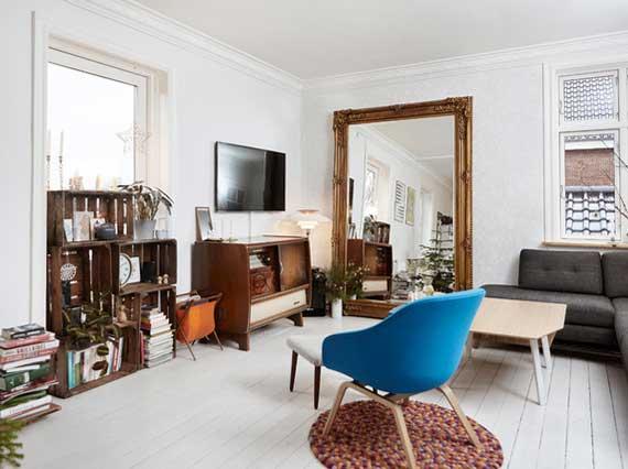 skandinavisches wohnzimmer interieur in weiß mit rustikaler wohndeko aus  holzakzenten,ganzkörperspiegel im verziertem rahmen, diy regal aus holzkisten und schönem polstersessel blau