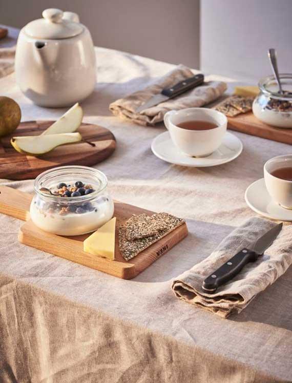 tisch rustikal und einladend decken mit einem schneidebrett-tischset, tischdecke und stoffservieten in beige