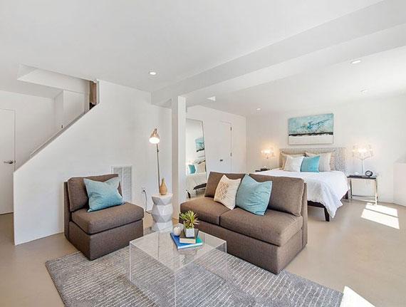 ein helles und einladendes gästezimmer im keller einrichten mit doppelbett und sitzecke mit ledersofa und couchtisch acrylglas