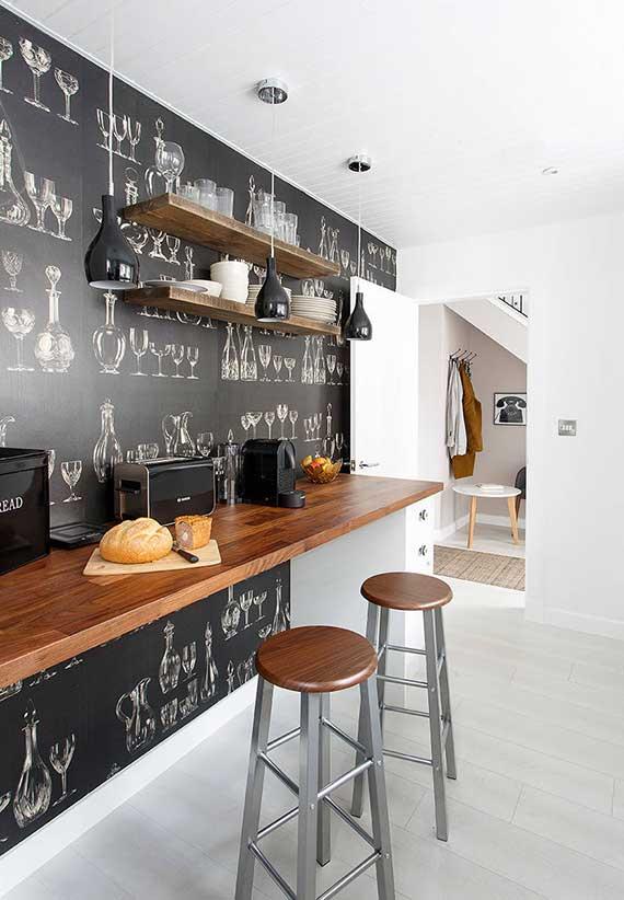 moderne kleine küche attraktiv gestalten mit schwarzer Fototapete glassware als akzentwand hinter holztheke mit runden barhockern holz