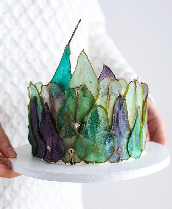 tortendekoration mit grünen und lilafarbigen birnenscheiben_eine gesunde snackdeko für edle herbstliche desserts