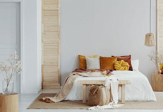 kleine schlafzimmer stilvoll gestalten mit weißen wänden, wohnaccessoires aus hellem holz und farbakzenten in orange und gelb