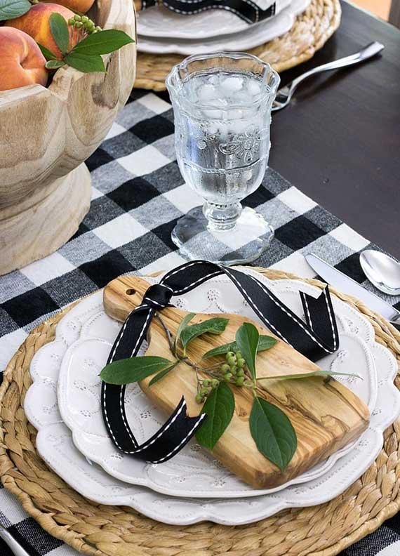 effektvolle platztellerdeko mit rattan-untersetzer, weißen porzellantellern und holzbrett mit schwarzem band und grünem beerenzweig