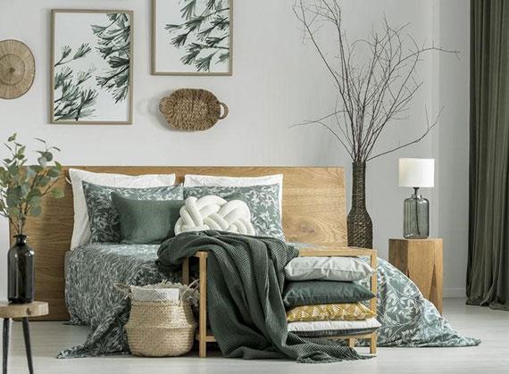 schickes schlafzimmer interieur gestalten mit schlafzimmermöbeln holz, zimmerdeko mit flechtwaren und hochwertiges bettwäsche in grün als frischer farbakzent zur wandfarbe weiß