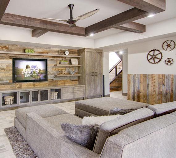 den keller einrichten wie ein gemütlicher schlaf- und unterhaltungsbereich im landhausstil mit weißen wänden,zwei liegesofas grau und tv wohnwand aus holz