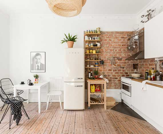 küche im skandinavischem wohnstil mit backstein-fototapete als wohndeko, retro kühlschrank weiß, kleine sitzecke mit modernen metallstühlen schwarz und holzbodenbelag