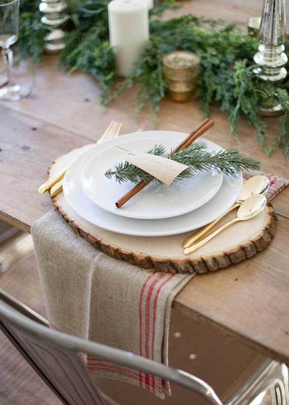tisch zu weihnachten im Bauernhaus Stil eindecken mit holz tischset, rupfen servietten, besteck in gold und namenskarte mit zimtstange und nadelbaumzweig im platzteller
