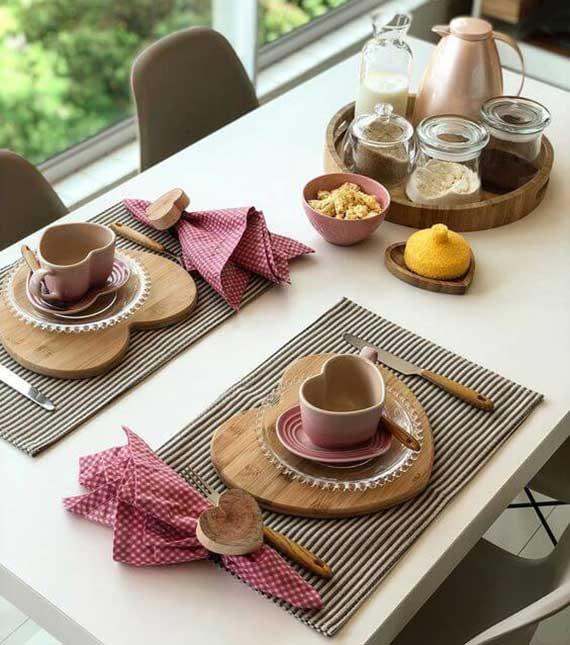 schlichte rustiake tischdeko idee für romantische frühstück am valentinstag mit herz-platzset aus holz und herfürmigen serviettenringen