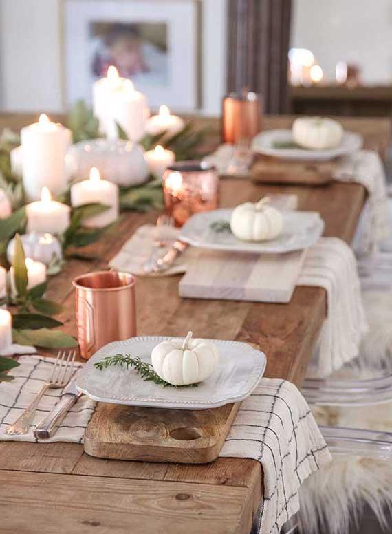 natürliche tischdekoration mit weißen mini kürbissen  und verschiedenen brotschneidebrettern als rustikales tischset