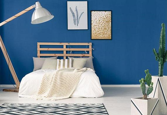 gestaltungsidee für wohlfühlendes ambiente im schlafzimmer mit wandfarbe balu, holzbett, vintage stehlampe holz und kakteen in weißen blumentöpfen
