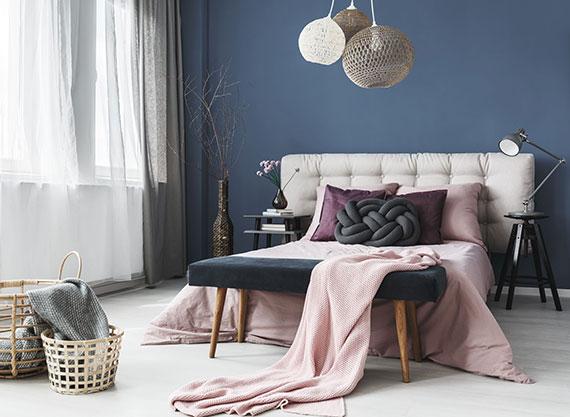 modernes schlafzimmer gestalten mit wandfarbe dunkelblau, weißem bodenbelag, garninen in weiß und grau, bett mit polsterkopfteil in weiß und bettbezug in pink