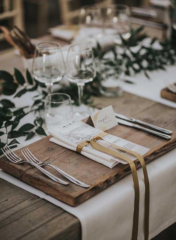 rustikale hochzeitdeko idee mit einfachem holzbrett tischset und grüne tischdeko mit zweigen auf weißer tischdeke