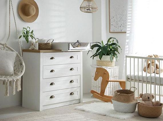 ein gemütliches babyzimmer gestalten mit weißem gitterbett, komode mit wickelaufsatz, hängesessel zum stillen und weiden aufbewahrungskörben