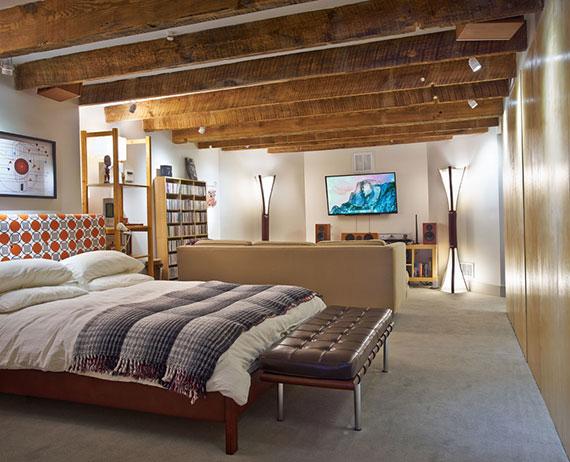 einladendes gästezimmer im keller einrichten mit doppelbett, 3er sofa mit tv-regal, kleiner bibliothek und leuchten zwischen holzdeckenbalken
