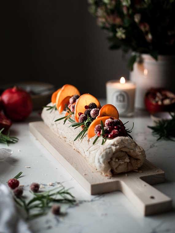 coole ideen für festliche tischdekoration im winter mit einem schneidebrett aus holz, frisches wintergrün, kerzen und granatäpfeln