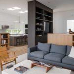 praktische und moderne wohnzimmereinrichtung mit raumteiler-regal schwarz und holzschränken mit viel stauraum
