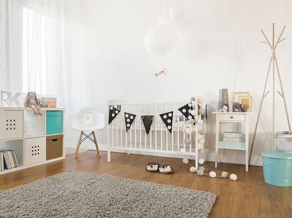 praktische babyzimmer ausstattung mit babybett, stauraummöglichkeiten und sessel zum stillen