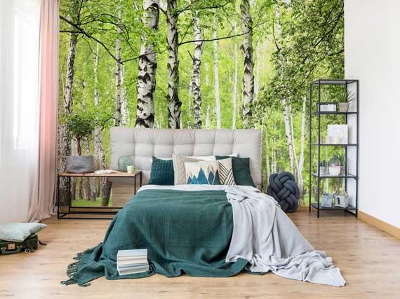 coole schlafzimmer wohnideen für wohnliche und einladende einrichtung mit holzbodenbelag und waldtapete hinter doppelbett mit weißem polsterbettkopfteil