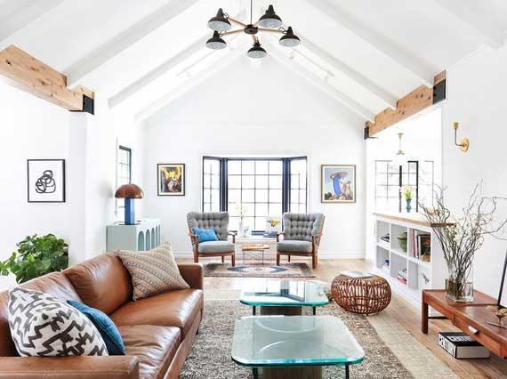 gemütliches wohnzimmer im farmhaus wohnstil mit ledersofa braun, zwei glaskaffeetischen, rattanhocker und verschiedenen regalmöbeln als staufläche für zahlreiche gegenstände