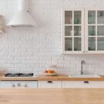 moderne und helle küchengestaltung mit akzentwand aus weißen ziegeln, küchendesign im klassischen stil mit weißen küchenschränken und holz-arbeitsplatte