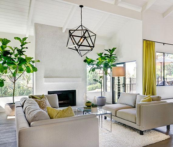 stilvolle wohnzimmer dekoration mit großen grünpflanzen beidseitig eines kamins