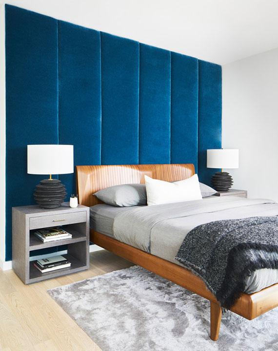 moderne gestaltungsidee für mehr entspannung im schlafzimmer mit akzentwand aus gepolsterten wandpaneelen in blau