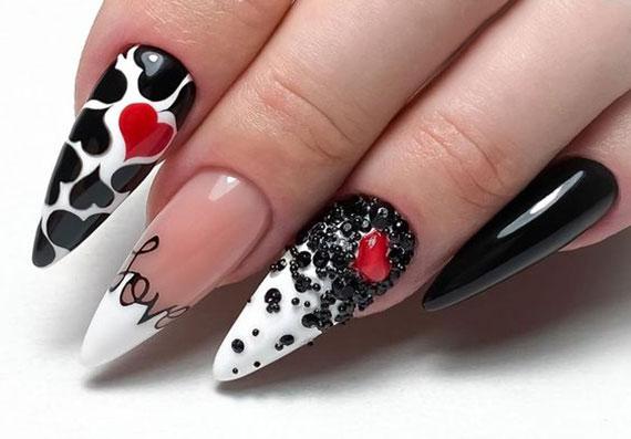 attraktive nagelkunst in schwarz und weiß mit strasssteinen und roten herzen