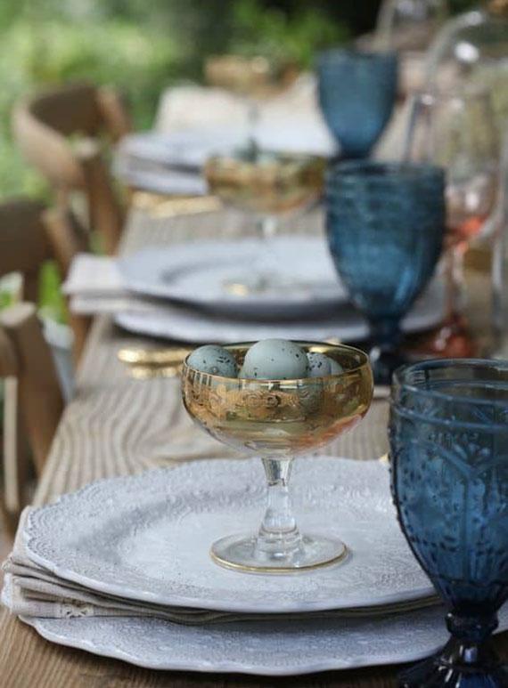 idee für stylische ostertafel dekoration in blau und gold mit Wachtel-Ostereiern im glas