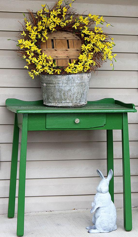 garten und terrasse einladend und osterlich dekorieren mit osterhase, diy kranz aus frühlingszweigen und metalleimer auf grünem holztisch