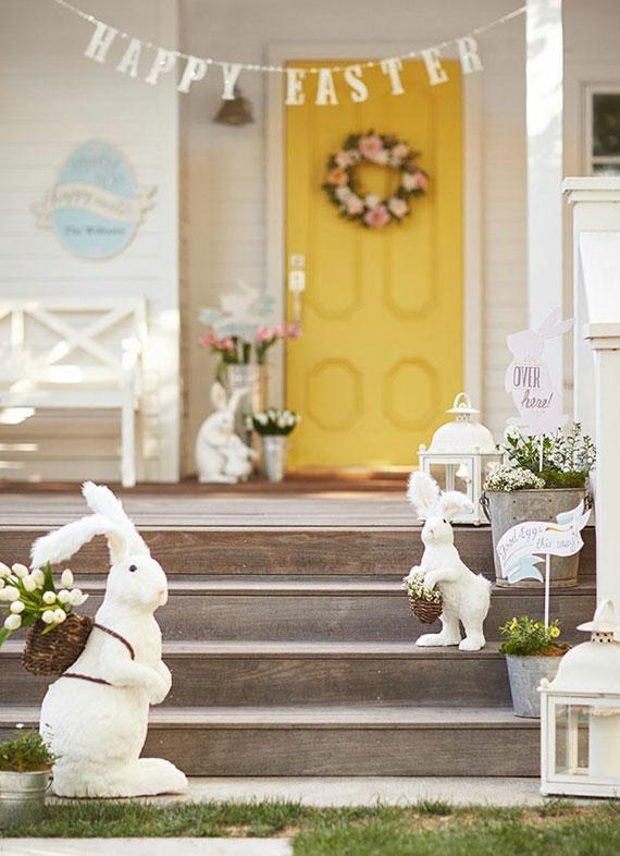 eingangsbereich osterlich dekoriren mit Girlande, osterhase figuren und weißen tulpen in weidenkörben