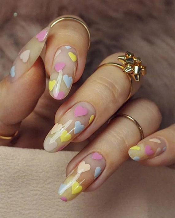 fröhliche valentinstag nageldesign ideen mit herzen in pastellfarben auf transparentem nagellack