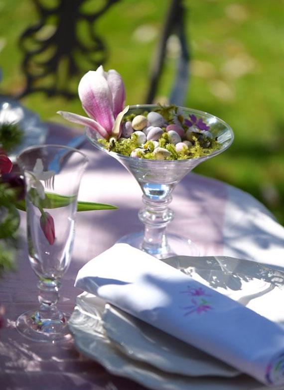 osterfest im garten feiern und eine festliche tafel mit magnolie-blüten und osterei bonbons als platzteller deko arrangieren